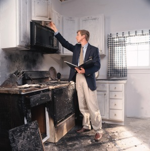 dr_person_assessing_kitchen_fire_damage
